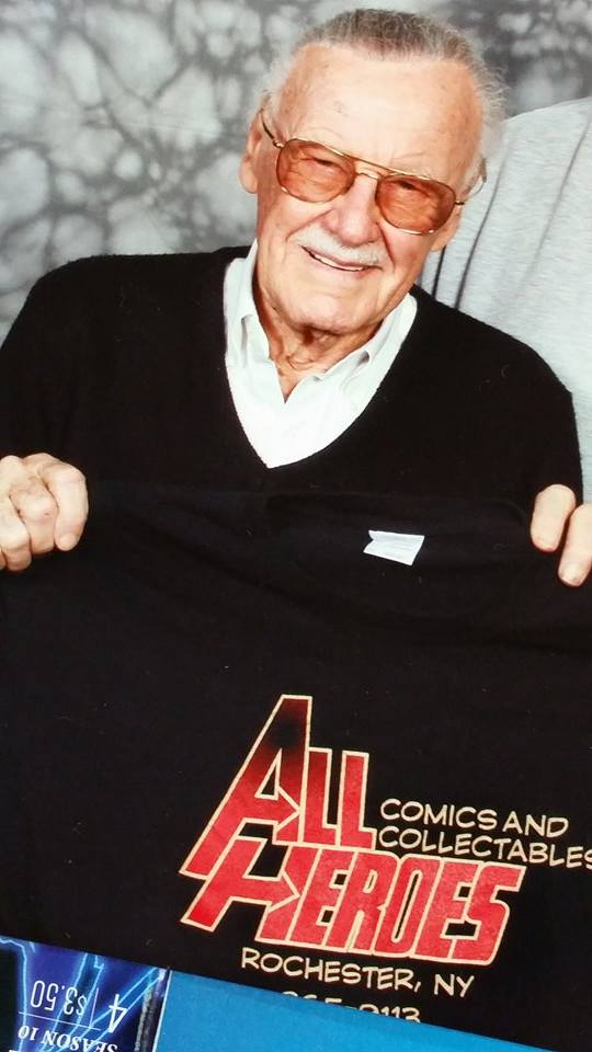 Stan Lee holding up an All Heroes Comics shirt.